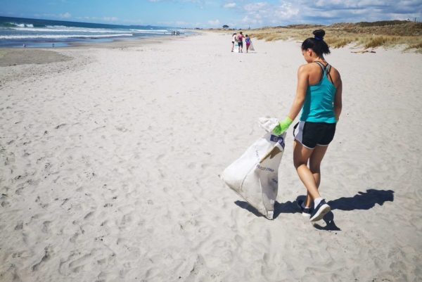 Young university student walks Mount Maunganui Beach with a rubbish bag on a Love Your Coast beach clean up