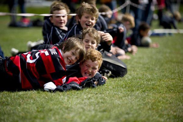 Kids in rugby uniform playing at the side line