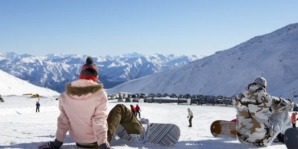 Students with snowboards sitting admiring the view at the Remarkables